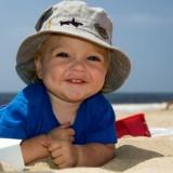 Plaża, słońce, uśmiechnięty bobas - obowiązkowo w czapeczce. Wakacje w pełni